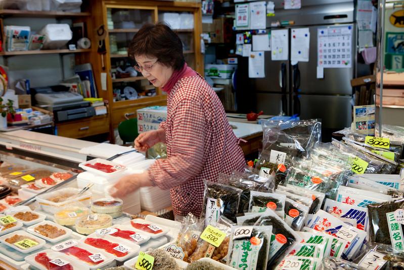 """""""Non ci sono più le navi da pesca. I prodotti che ho qui sul banco sono le ultimi cose che avevo nel magazzino, dopo non avrò niente da vendere."""" dice Fusako Kikuchi, 68 anni, nel mercato di pesce di Kamaishi. Ha perso il suo fratellino """"bonaccione"""" della città Yamada per colpa dello tsunami, le lacrime si sono ormai asciugate. """"Finche posso lavorare lavorerò, perché quello che dobbiamo fare adesso è andare avanti."""" Dice con il sorriso."""