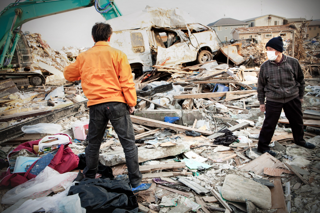 """82 year-old Eiji Suda is looking for his house, which was washed away by the tsunami, with his son. Until now he has only found the roof, 200 meters from the foundation. """"I was saved by a hair's breath. If I had waited five minutes more, I would have been carried away by the water"""". He used to work in a stationery shop with his wife, selling school articles, little objects and cosmetics. Now he is living with his son."""