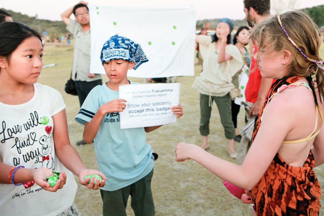 """Soraris 11 anni (senistra), Ryou 11anni (destra ) sono i figli dei fondatori Wataru Iwata e Aya Marumori di CRMS, prendono l'iniziativa nella manifestazione, raccolgono i fondi in cambio dei badge scritto""""NO Nuke Fukushima"""". Nella Boom Festival di Idana-a-Nova."""
