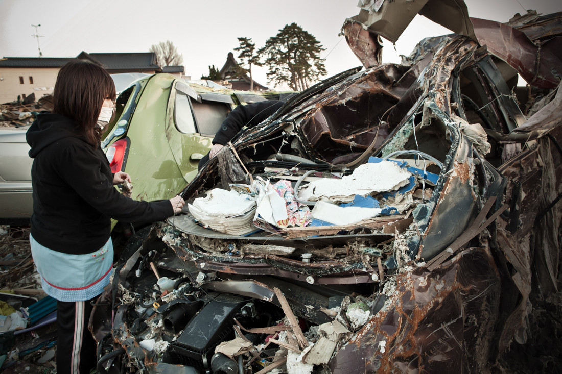 Una ragazza ha trovato la sua macchina e cerca di tirare fuori gli oggetti personali.
