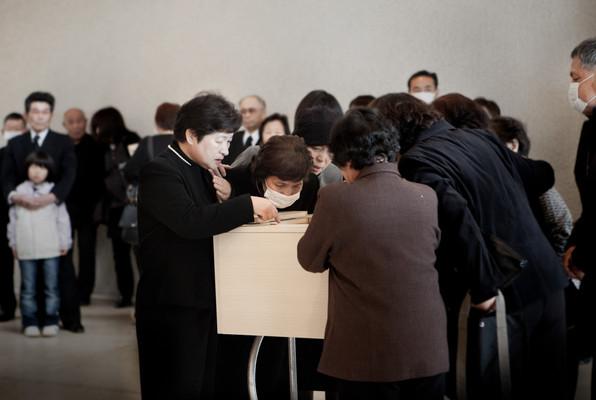 La celebrazione del funerale di una vittima dello tsunami. L'ultimo saluto attraverso una piccola apertura della bara. Nel crematorio di Kesennuma, prefettura di Miyagi.