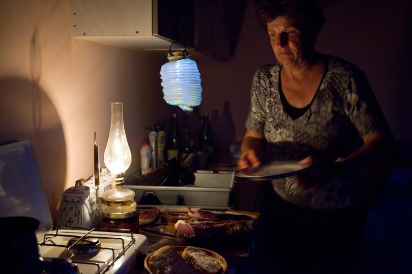 Nella sua cucina, la signora Lončar prepara la cena a lume di lampada. Prima della guerra c'era la corrente elettrica.