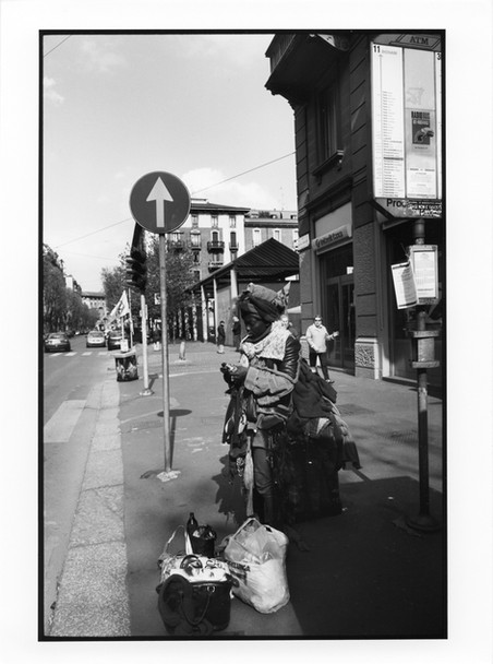 """Il suo tempo passa molto lentamente. Quando se la sente, inizia un nuovo """"Viaggio"""". Così lei va a vagabondare per Milano con il suo zaino incredibilmente pesante, diverse borse e sacchetti. Dentro questi bagagli ci sono sempre 5 o 6 bottiglie di birra, vestiti, roba da mangiare, giornali, sacchetti, radio, pacchetti di sigarette vuoti.. i suoi """"tesori"""", la raccolta del passato. Porta il suo fardello ovunque vada, senza lamentarsi e scoraggiarsi. """" Mi piace viaggiare. Oggi sono andata fino in Giamaica!"""""""