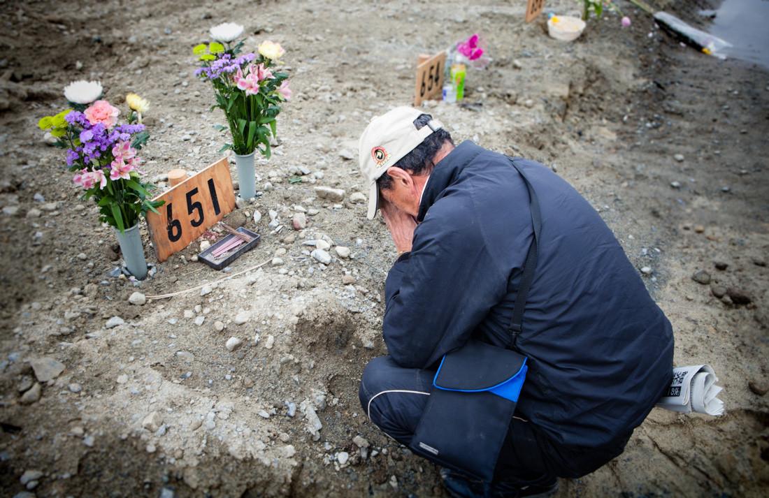 """Hideyuki Hasebe, 70anni, pregava sulla tomba del suo amico di università Tsukatoshi Niizuma, 61anni. Nella tomba di fianco giace il padre, la madre non è stata ancora trovata. """"L'intera famiglia Niizuma se ne è andata."""" dice fra le lacrime. """"Non ho sentito l'allarme, ho portato mia madre al primo piano di casa e l'acqua è arrivata comunque fino al petto. Lo Tsunami non fa rumore, e' giunto con il silenzio e ha portato via tutto."""" Anche suo cugino è ancora disperso, sua moglie tutti giorni gira tra gli obitori per cercarlo."""