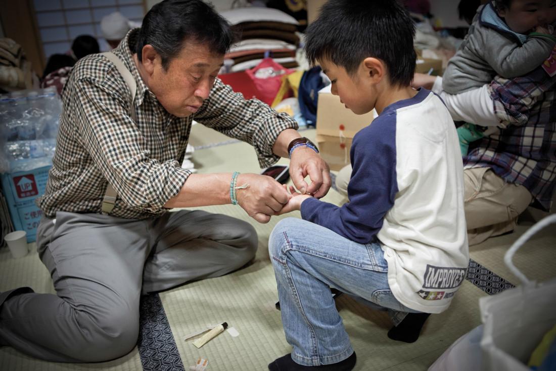 Un signore medica una ferita di un ragazzino.
