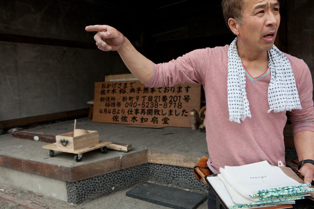 Yu Sasaki pubblica su un cartellone della famiglia illesa e della riapertura del negozio di paravento. Dopo lo Tsunami hanno trovato una vittima nella propria casa, una signora che abitava di fronte. Kamaishi