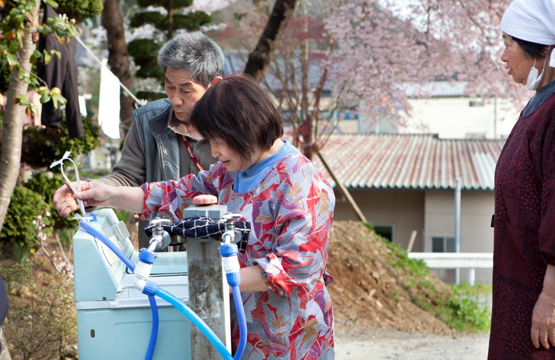 Si illuminano i visi dei rifugiati che hanno appena ricevuto in dono una lavatrice degli anni settanta usata. Da più di un mese, a causa della non disponibilità di acqua potabile ed elettricità, lavavano a mano i loro bucati con l'acqua di riserva. Nel giardino del tempio Jounenji – Rifugio. Kesennuma.