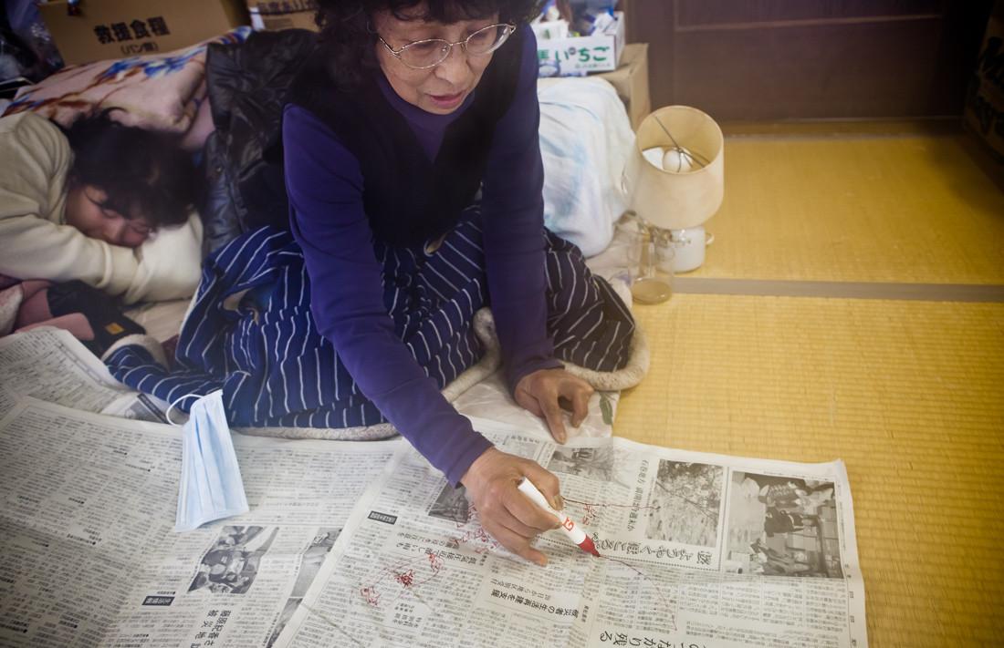 """Al momento del Terremoto di Magnitudo 9, Motoko Iri lavorava nella Fabbrica del Prodotto Marino vicino al porto per pescherecci di Ishinomaki. Mentre stava tornando a casa in auto lo Tsunami le è comparso nello specchietto retrovisore, subito è stata sommersa fino alla cintola, poi salvata. Correndo sul sentiero di un'altura è iniziato a nevicare, in seguito ha passato tutta la notte a tremare nella palestra comunale. Ha perso la sorella, il fratello e il lavoro perché la fabbrica è distrutta. La sua casa si è inclinata ed è stata parzialmente distrutta, pur essendo inabitabile deve continuamente pagarne il mutuo. """"Chiunque ha perso la casa è nella stessa situazione"""" spiega come se si fosse già rassegnata. Adesso vive con sua figlia da un mese mezzo nel rifugio al Liceo Ishinomaki. Si spera di vincere il sorteggio per gli alloggi temporanei, le possibilità sono una su dieci."""