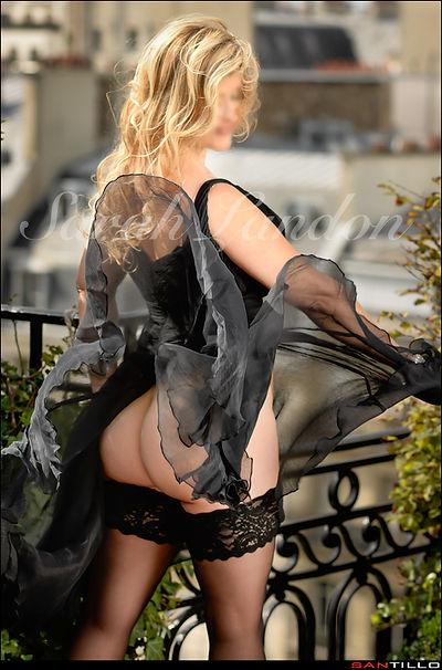Mature Elite Tampa VIP Companion Sarah Landon on a balcony in Paris with her diaphanous dress flying in the wind