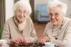 Two Senior Women Playing Dominoes At Day