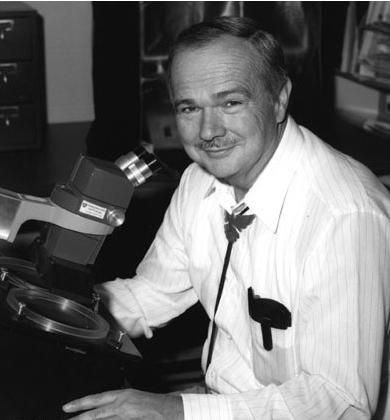 um homem branco de meia idade com um bigode fino, vestindo uma camiseta clara. A sua frente um microscópio.. foto em preto e branco.