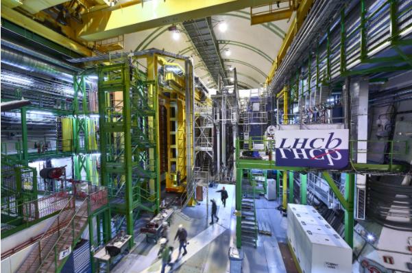 Um grande estrutura de metal encontra-se a esquerda, muito maior que as pessoas no chão. Na direita, temos uma placa com o logo do experimento LHCb.