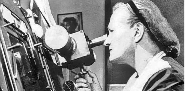 Foto em preto e branco de uma mulher operando um telescópico. A esquerda da foto, uma senhora de cabelo preso está olhando através da lente de um grande telescópio que ocupada a metade esquerda da foto