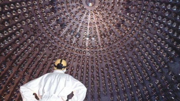 Um homem de costas com roupas de proteção olha para uma parede cheia de detectores que parecem lâmpadas redondas. Foto do experimento Borexino