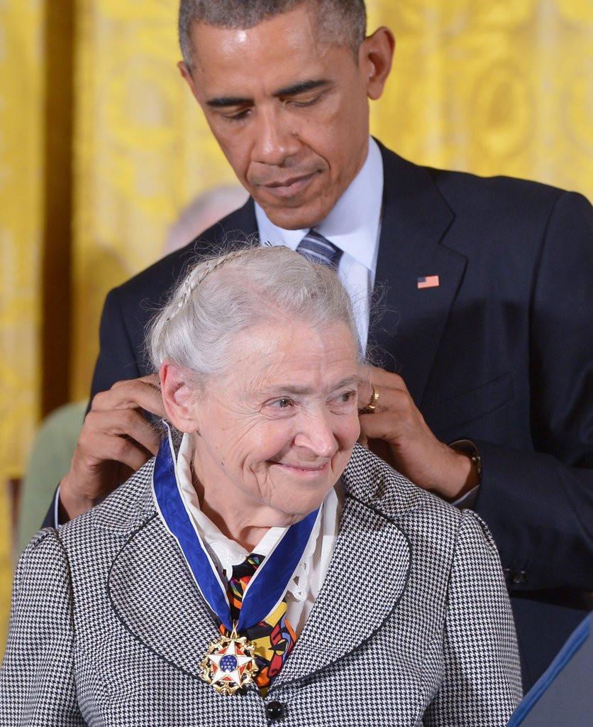 Uma senhora branca de cabelos grisalhos aparece sorrindo, atrás um senhor negro coloca uma medalha em seu pescoco. A senhora é a Física Mildred Dresselhaus e o senhor é o ex-presidente estadunidense Barack Obama