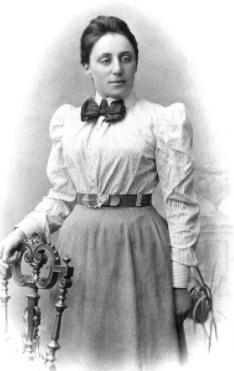 Uma foto em preto e branco de uma mulher com cabelo preso, camisa de manga comprida com uma gravata borboleta e uma saia comprida pressa por um cinto. Ela aparenta estar posando para a foto, com a mão direita apoia em uma cadeia com diversos detalhes de marcenaria