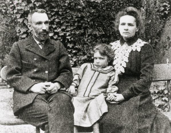 Foto em preto e branco com três pessoas, da esquerda para direita, um senhor de cabelo curto, barba e roupas sociais; no meio uma menina pequena com olhar curioso e um vestido e na direita uma mulher com cabelos até o ombro levemente arrepiados e um vestido.