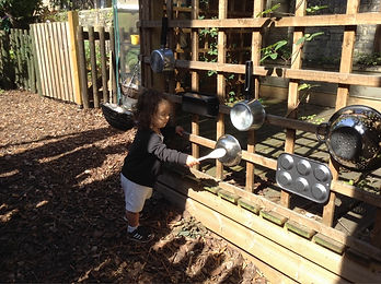 Baby playing in Harvey Road Nursery's garden mud kitchen