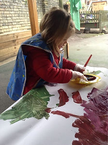 Painting and messy play at Harvey Road Nursery in Cambridge, nursery garden