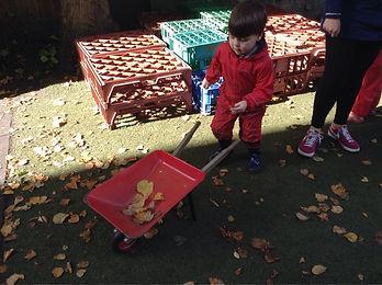 Child playing with wheelbarrow in garden at Harvey Road Nursery in Cambridge