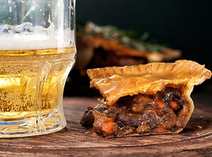 Piece of Australian meat pie with a glas