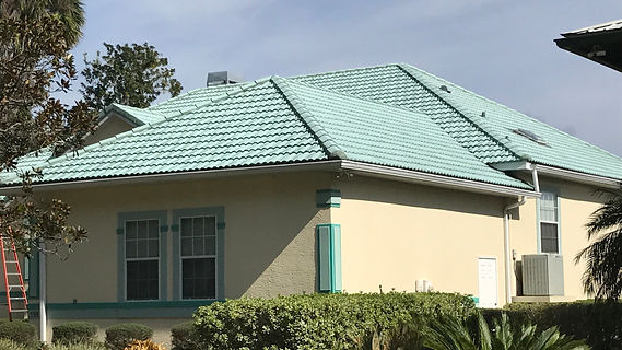 Beautiful light green tile roof on residential home with a blue skyline. We just pressure washed the entire home including the tiles