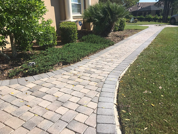 Brick Paver sidewalk that is faded from the sun and you see landscaping and the front of a house