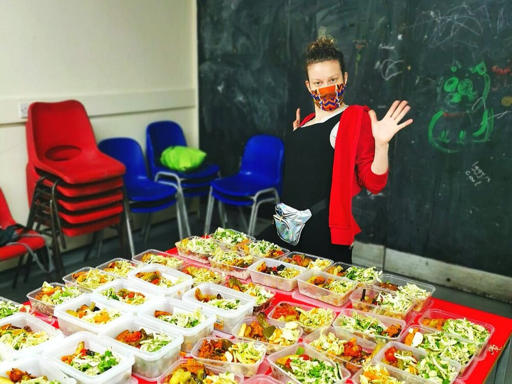 FEAST!  volunteer showing off a table full of food in takeaway containers