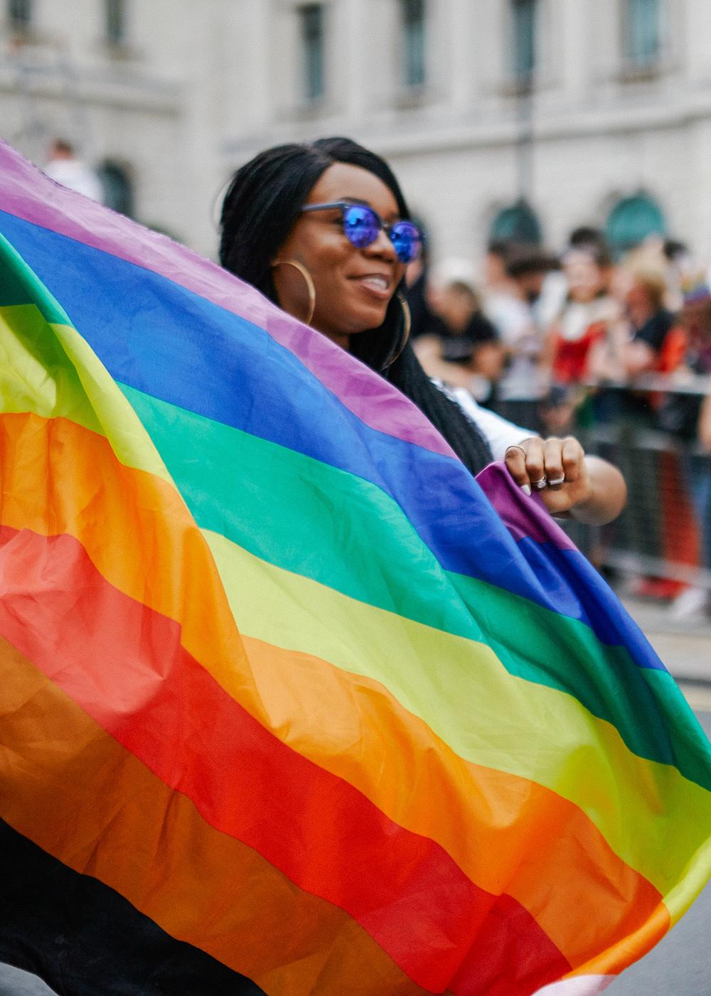 woman holding a pride rainbow flag
