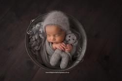 Newborn baby in bucket pose