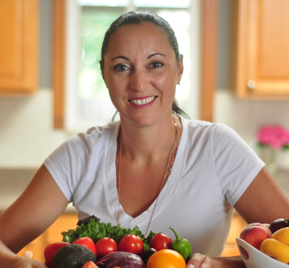 Headshot of Josie in kitchen with bowl of vegetables in front of her