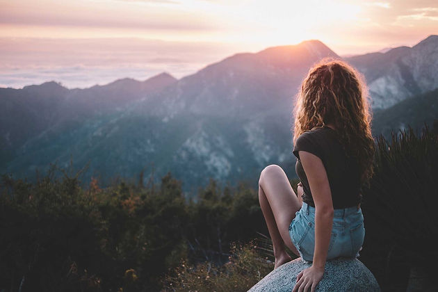 Image of woman sitting on a rock ang gazing out to the sun rising over a mountain top
