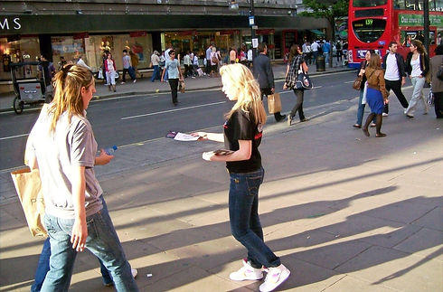 a woman handing out leaflets
