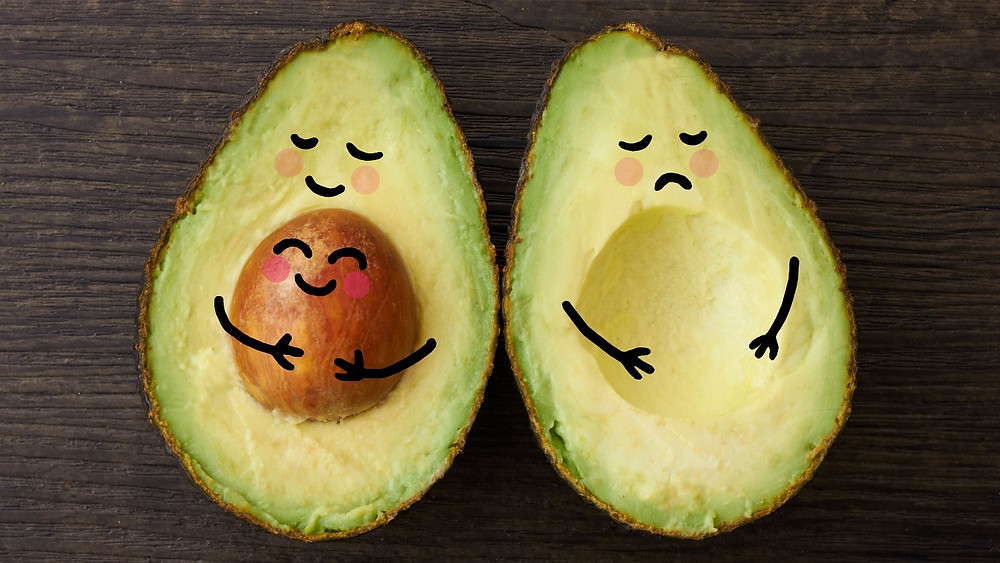 Avocado split in half, one with happy face, one with sad face drown on