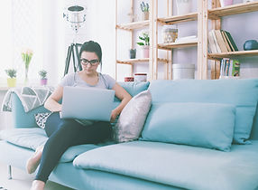 Young woman using laptop while sitting o