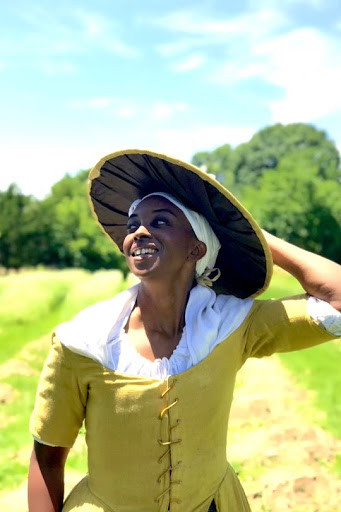 A woman dressed in 18th century clothing holds her hat and smiles while standing near a field