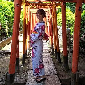 Una bella ragazza in posa sotto i torii