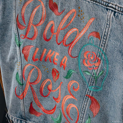 """A customised denim jacket inspired by the Disney Princess Belle from Beauty and The Beast. This hand-painted jacket contains the quote """"Bold Like a Rose"""" in elegant script lettering, embellished with rose petals and a rose in a cloche."""