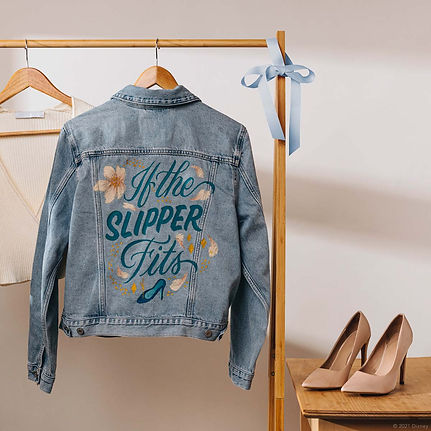 """A customised denim jacket inspired by the Disney Princess Cinderella from Sleeping Beauty.  This hand-painted jacket contains the quote """"If the Slipper Fits"""" in blue elegant script lettering, embellished with a glass slipper and gold sparkles."""