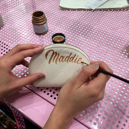 """A small leather pouch being hand-painted with the name """"Maddie"""" hand lettered in elegant b"""