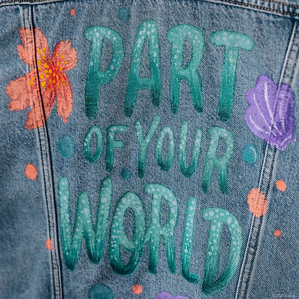 """A customised denim jacket inspired by the Disney Princess Ariel from The Little Mermaid. This hand-painted jacket contains the quote """"Part of Your World"""" in colourful block lettering, embellished with sea shells and a hibiscus flower."""