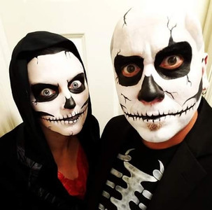 Image of two people face painted with skull makeup..