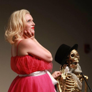 Image of a woman in a pink dress next to a golden skeleton.