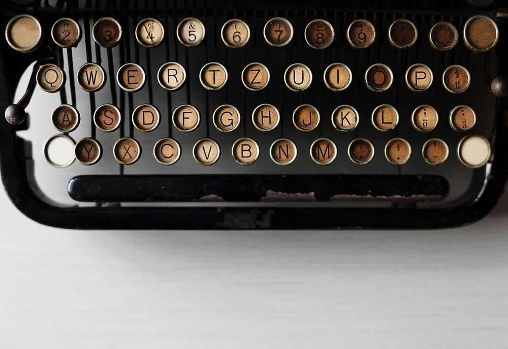 antique black typewriter with tan keys
