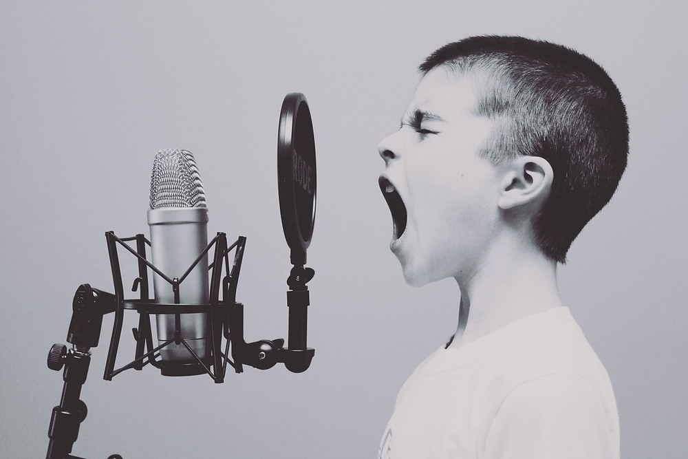 black and white image of boy yelling into microphone
