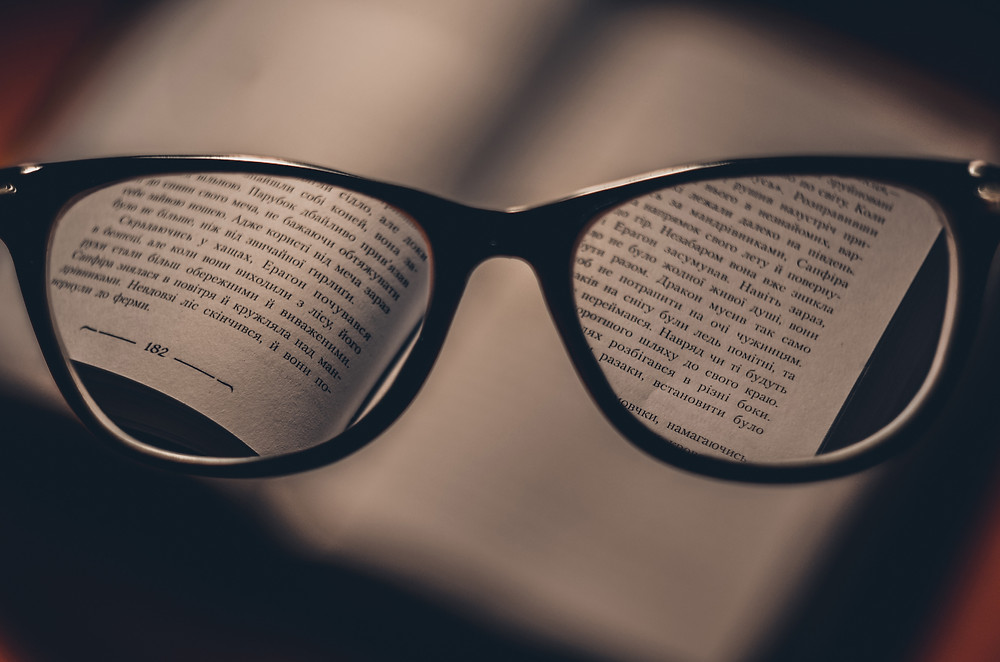 glasses in front of a book