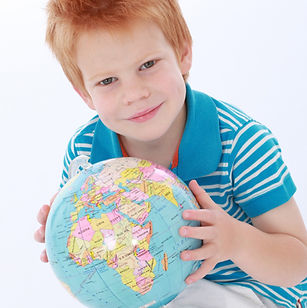 One cheeky red head boy wearing blue and white sitting with world atlas globe and smiling_edited.jpg