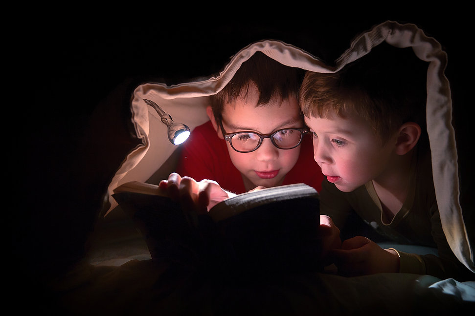 children engrossed in reading a book under the blanket. kids reading  in the bed with flashlight.jpg