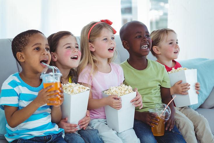 Happy kids enjoying popcorn and drinks w