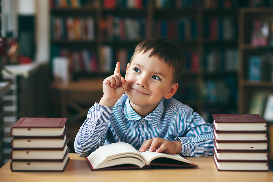 Smiling preschool european boy is staying at the table in the library with stacks of books...oo..jpg